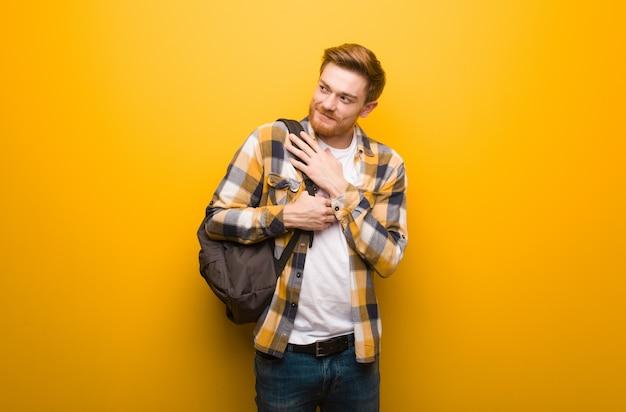 Jonge roodharige student man die een knuffel geeft