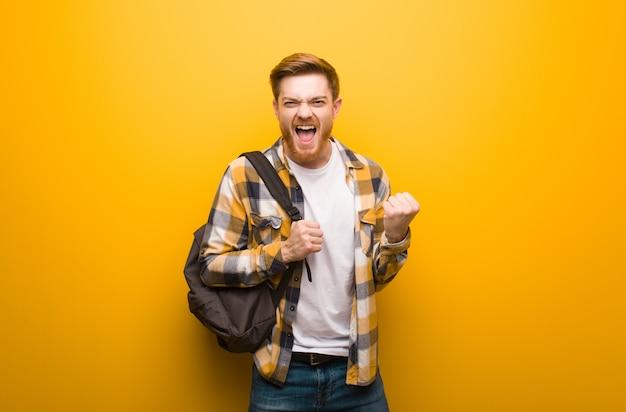 Jonge roodharige student man verrast en geschokt