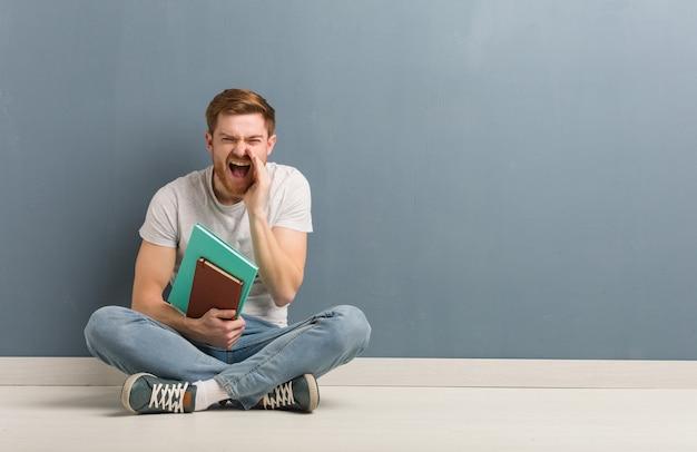 Jonge roodharige student man zittend op de vloer iets blij naar voren te schreeuwen. hij houdt boeken vast.