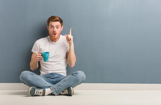 Jonge roodharige student man zittend op de vloer met een geweldig idee, concept van creativiteit. hij houdt een koffiemok vast.