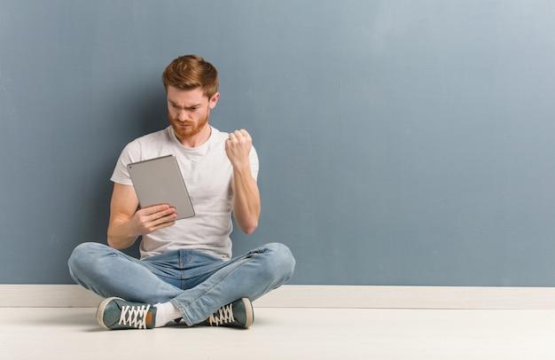 Jonge roodharige student man zittend op de vloer met vuist aan voorzijde, boze uitdrukking. hij houdt een tablet vast.