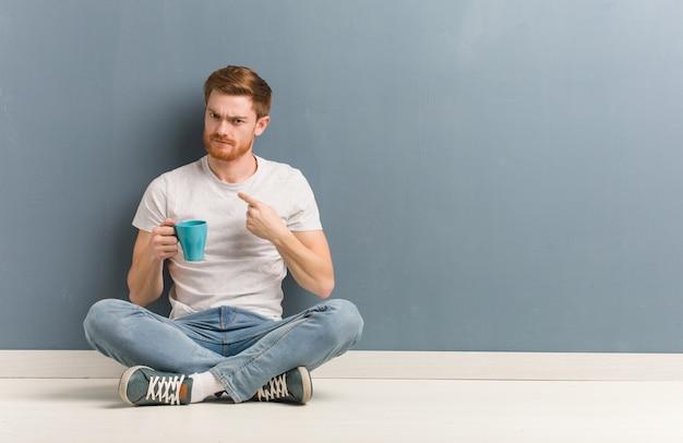 Jonge roodharige student man zittend op de vloer uit te nodigen om te komen. hij houdt een koffiemok vast.