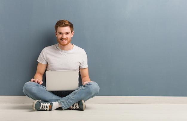 Jonge roodharige student man zittend op de vloer vrolijk met een grote glimlach hij houdt een laptop