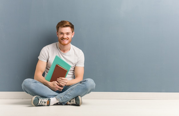 Jonge roodharige student man zittend op de vloer vrolijk met een grote glimlach