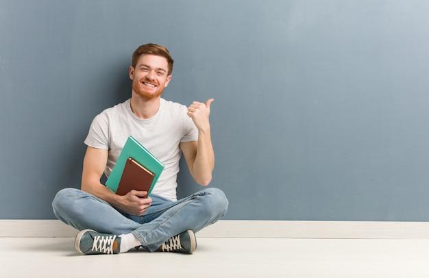 Jonge roodharige student man zittend op de vloer wijst naar de kant met vinger hij houdt boeken.