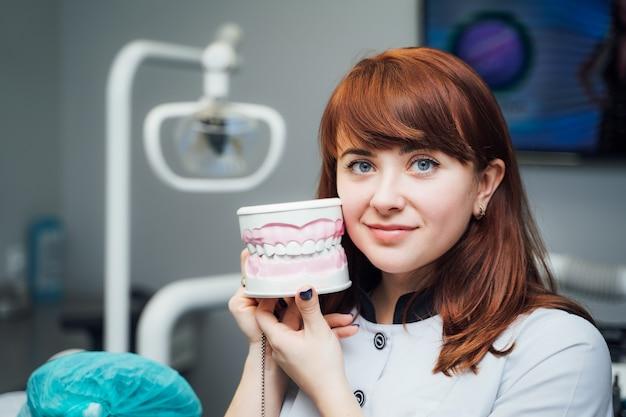 Jonge roodharige tandarts in de kliniek