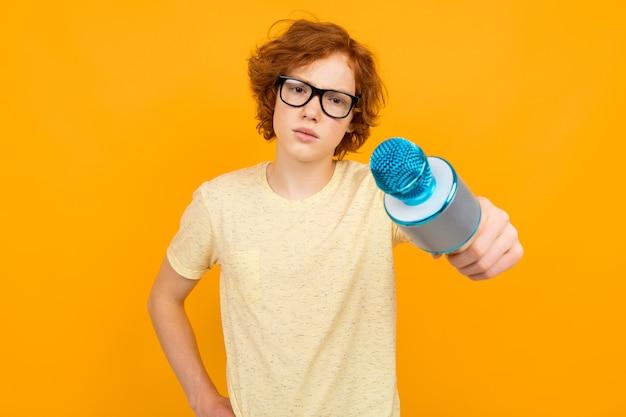 Jonge roodharige tiener in een overhemd en glazen op geel