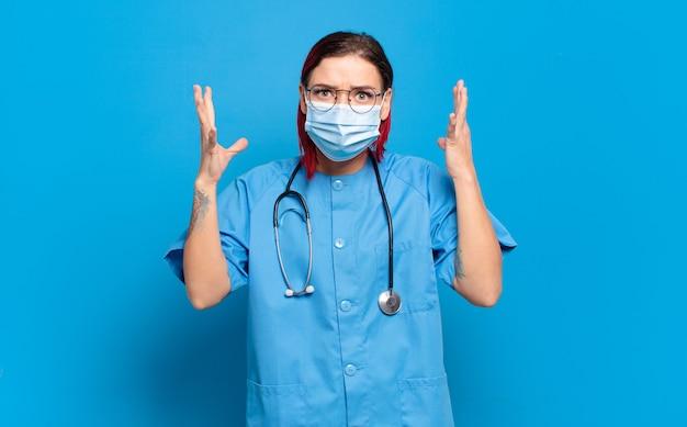 Jonge roodharige verpleegster die met handen in de lucht schreeuwt