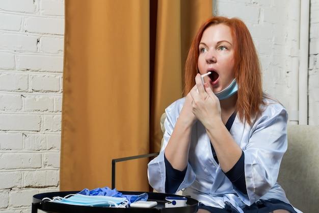 Jonge roodharige vrouw behandelt keelspray.