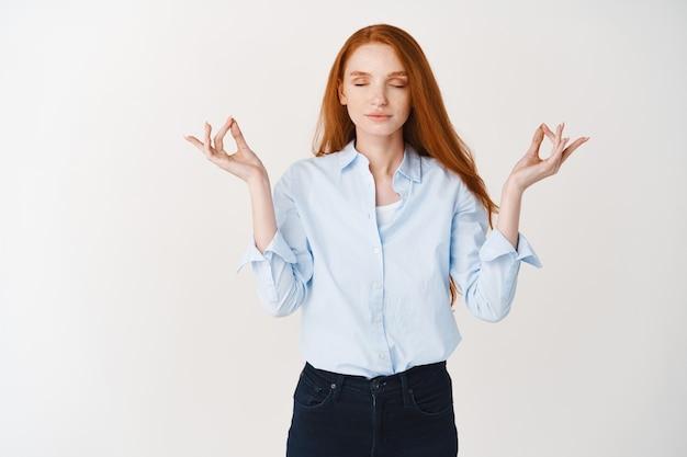 Jonge roodharige vrouw die kalm blijft met meditatie, sluit de ogen en spreidt handen in mudra om teken, oefen yoga tegen witte muur