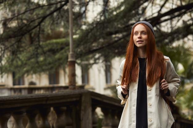 Jonge roodharige vrouw die loopt, geniet van het verkennen van nieuwe plaatsen die reizen en nieuwe plaatsen bezoeken met bac...