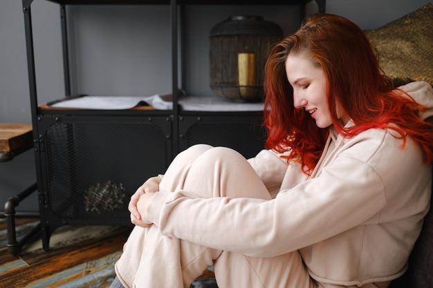 Jonge roodharige vrouw die vrije tijd thuis doorbrengt. sereen ochtenden. het concept en idee van een rustige ochtend, meditatie en ontspanning op een weekenddag