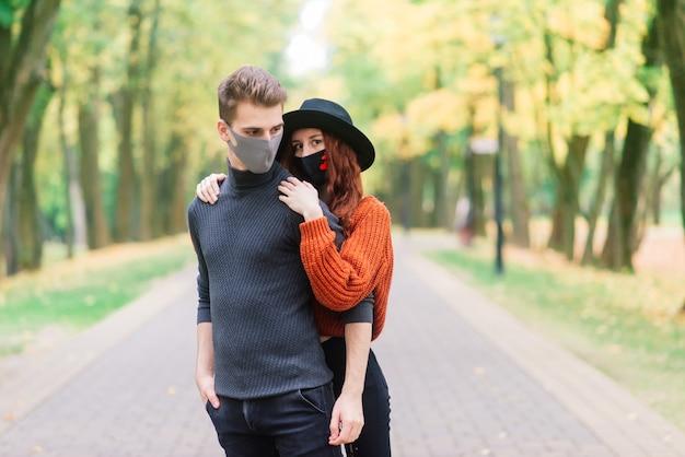 Jonge roodharige vrouw en vriend die medische maskers dragen