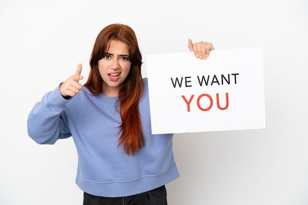 Jonge roodharige vrouw geïsoleerd op een witte achtergrond die we want you aan boord houdt en naar voren wijst