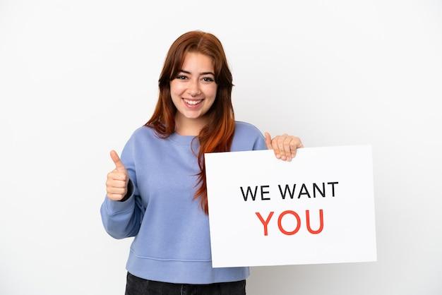 Jonge roodharige vrouw geïsoleerd op een witte achtergrond houden we want you bord met duim omhoog