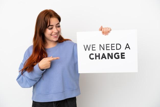 Jonge roodharige vrouw geïsoleerd op een witte achtergrond met een bordje met de tekst we need a change en erop wijzend