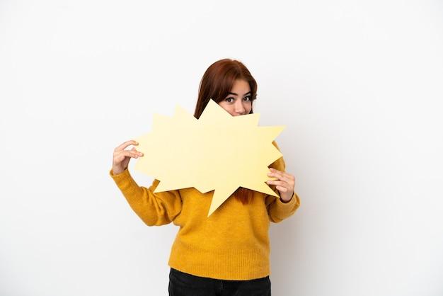 Jonge roodharige vrouw geïsoleerd op een witte achtergrond met een lege tekstballon en verstopt zich erachter