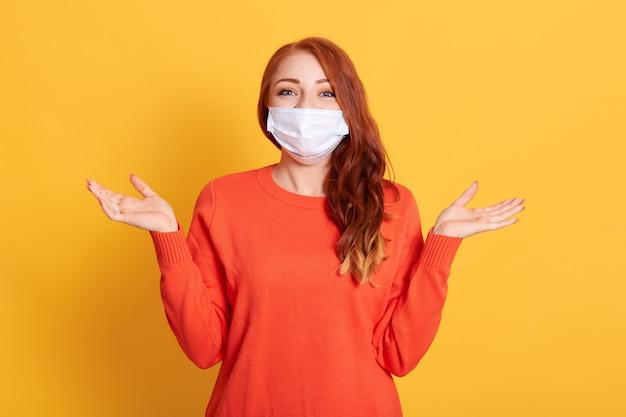 Jonge roodharige vrouw in beschermend medisch masker handen opzij spreiden, vrouwtje draagt oranje casual trui poseren geïsoleerd op gele achtergrond.