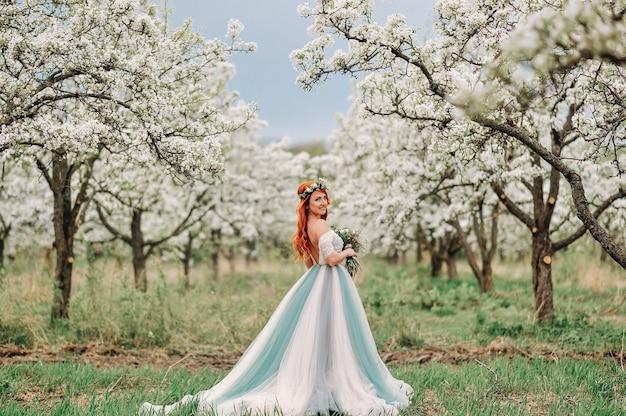 Jonge roodharige vrouw in een luxe jurk staat in een bloeiende tuin