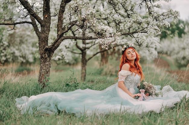 Jonge roodharige vrouw in een luxe jurk zit op het gras in een bloeiende tuin