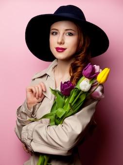 Jonge roodharige vrouw in mantel met boeket tulpen op roze
