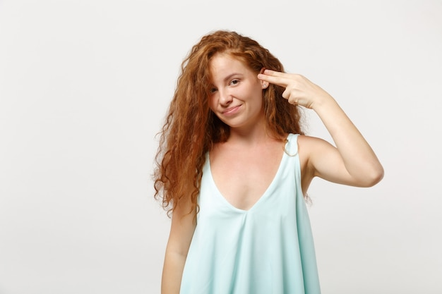 Jonge roodharige vrouw meisje in casual lichte kleding poseren geïsoleerd op een witte achtergrond studio portret. mensen levensstijl concept. bespotten kopie ruimte. wijs met de vingers naar het hoofd alsof ze op het punt staat zichzelf neer te schieten.