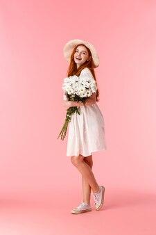 Jonge roodharige vrouw met bloemen boeket op roze
