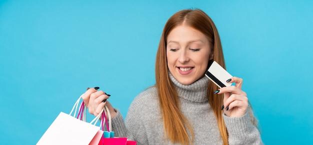 Jonge roodharige vrouw met boodschappentassen en een creditcard