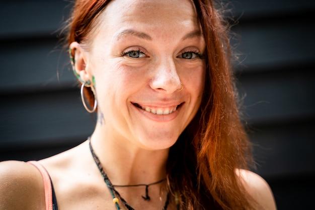 Jonge roodharige vrouw met tatoeages en lachende piercings glimlachen
