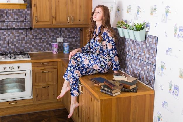 Jonge roodharige vrouw ontspannen thuis met boeken