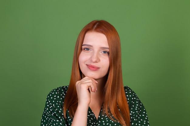 Jonge roodharige vrouw op groene muur doordachte ondervraging