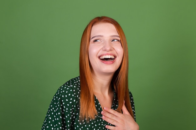 Jonge roodharige vrouw op groene muur lacht en lacht, in een goed humeur, positieve emoties