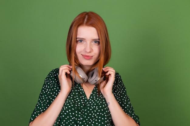 Jonge roodharige vrouw op groene muur met draadloze koptelefoon kijkt naar de camera met een zelfverzekerde glimlach