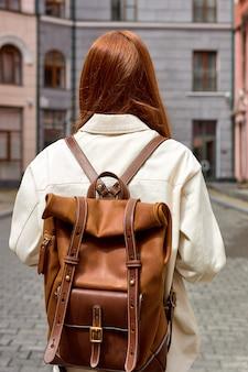 Jonge roodharige vrouw reiziger met lederen rugzak, travel concept. achteraanzicht