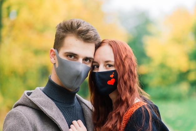 Jonge roodharige vrouw zet op een gezichtsmasker tijdens het wandelen met jonge man in herfst park.