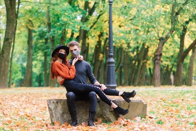 Jonge roodharige vrouw zet op een gezichtsmasker tijdens het wandelen met jonge man in herfst park