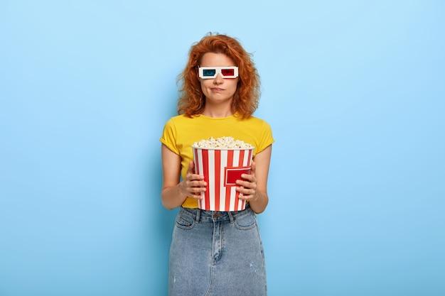 Jonge roodharige vrouwelijke filmbezoeker verveelt zich bij het kijken naar een historische film, bezoekt de bioscoop