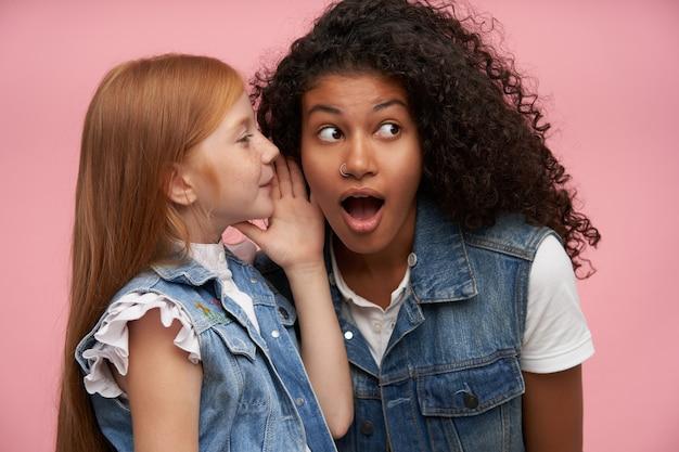 Jonge roodharige vrouwelijke jongen in vrijetijdskleding vertrouwt iets privé met verrast jonge donkerhuidige krullende brunette dame, staande tegen roze