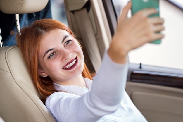Jonge roodharige vrouwenchauffeur die selfies met haar mobiele telefoonzitting achter het wiel van de auto in spitsuuropstopping nemen.