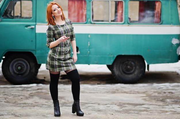 Jonge roodharige vrouwendame met mobiele telefoon en hoofdtelefoons, die op gecontroleerde kleding in oude uitstekende minivan bus draagt.
