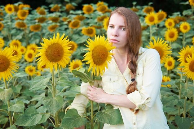 Jonge roodharige wit meisje in zonnebloem veld met gevlochten kapsel