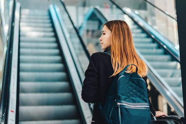 Jonge roodharige yong toeristenvrouw met een rugzak die een roltrap in de internationale luchthaventerminal nadert