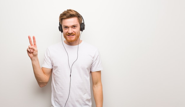 Jonge roodharigemens die nummer twee tonen. luisteren naar muziek met een koptelefoon.