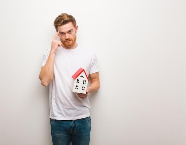 Jonge roodharigemens die over een idee denkt. een huismodel vasthouden.