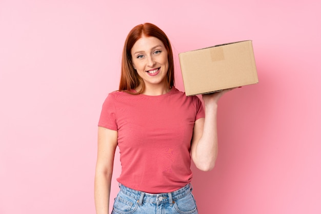 Jonge roodharigevrouw die een doos houden om het naar een andere plaats te verplaatsen