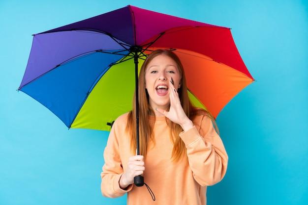 Jonge roodharigevrouw die een paraplu over geïsoleerde muur houden die met wijd open mond schreeuwen