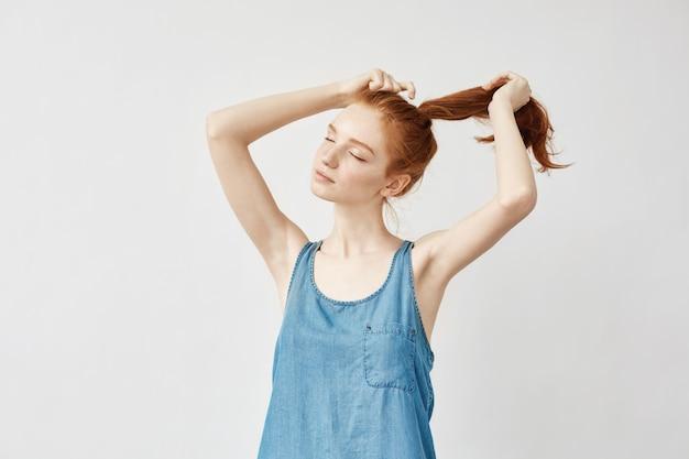 Jonge roodharigevrouw die haar kapsel corrigeert.