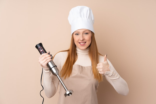 Jonge roodharigevrouw die staafmixer met omhoog duimen gebruiken omdat iets goeds is gebeurd