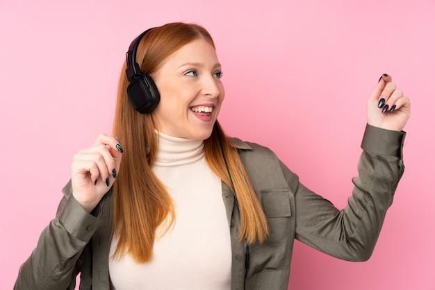 Jonge roodharigevrouw het luisteren muziek en het dansen