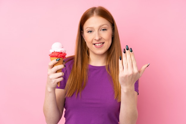 Jonge roodharigevrouw met een cornetroomijs over geïsoleerde roze muur die met hand uitnodigt te komen